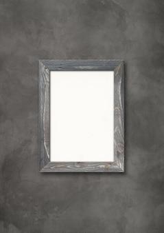 Ancien cadre photo en bois rustique gris accroché sur un mur de béton foncé. modèle de maquette vierge