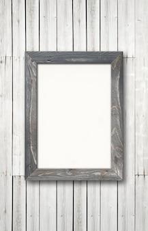 Ancien cadre photo en bois rustique gris accroché à un mur en bois.