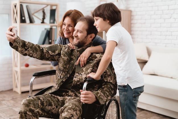Un ancien combattant en fauteuil roulant fait un selfie avec sa famille.