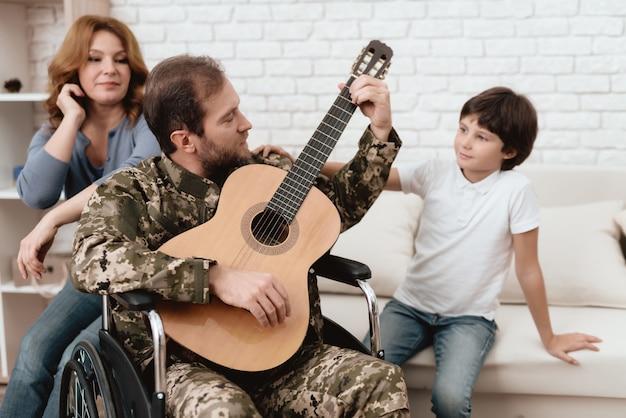 Un ancien combattant joue de la guitare une femme et son fils écoutent sa musique