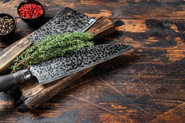 Ancien couperet et couteau à viande de boucherie. table en bois foncé. vue de dessus.