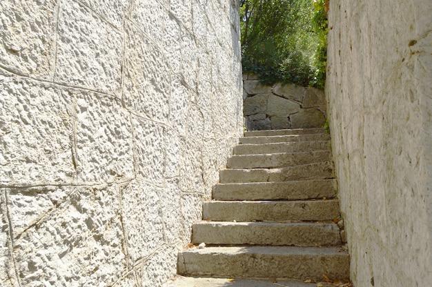 Ancien escalier étroit avec mur de pierre des deux côtés, qui mène vers le haut, éclairé par la lumière du soleil