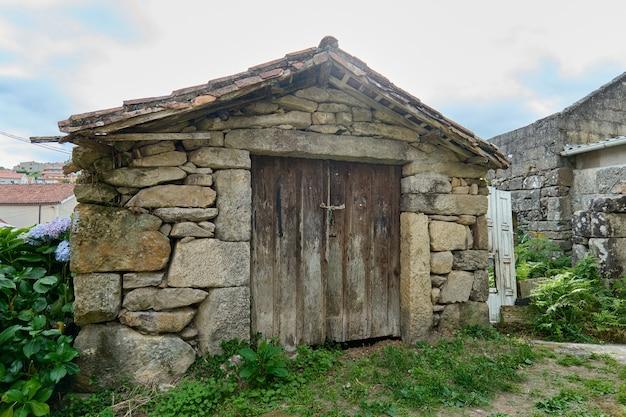 Ancien hangar abandonné fait de ton avec une porte en bois
