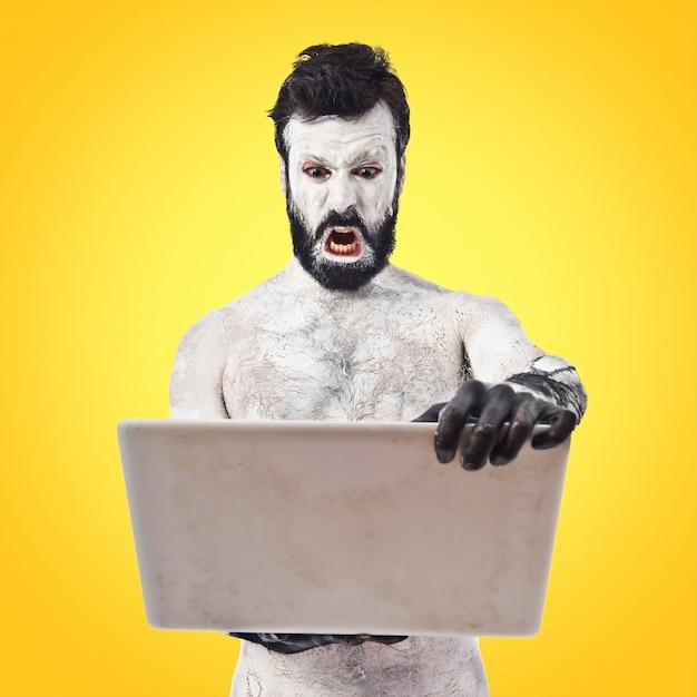 Ancien homme de la civilisation avec un ordinateur portable sur fond coloré