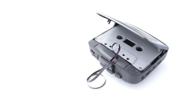 Ancien lecteur de cassette et cassette isolé sur une surface blanche