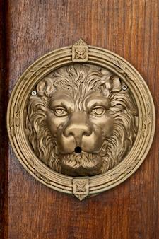 Ancien lion de bronze italien sur fond marron en bois