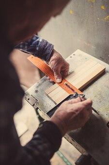 Ancien menuisier travaillant avec du bois, teinté rétro