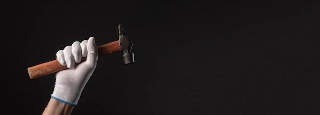 Ancien outil de marteau avec manche en bois à la main dans un gant de construction gros plan sur fond noir avec fond.