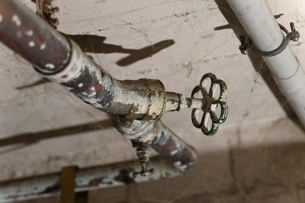 Ancien robinet d'eau en bronze sur la toile d'araignée