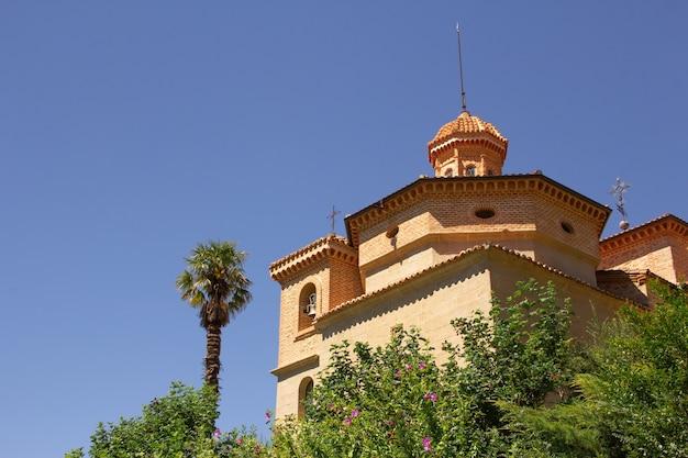 Ancien sanctuaire entre arbres et palmiers.