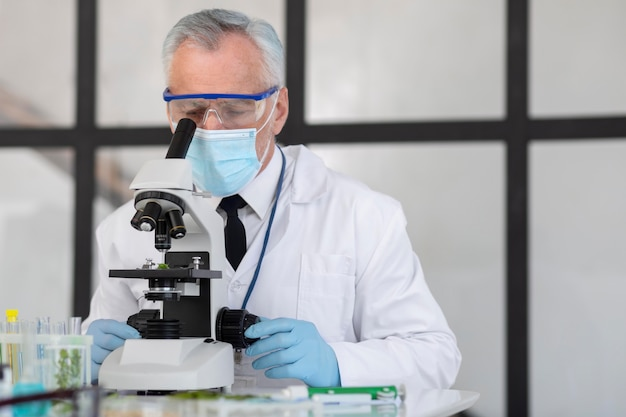 Ancien scientifique travaillant avec microscope