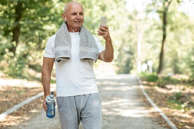 Ancien se reposant en regardant son téléphone dans la forêt