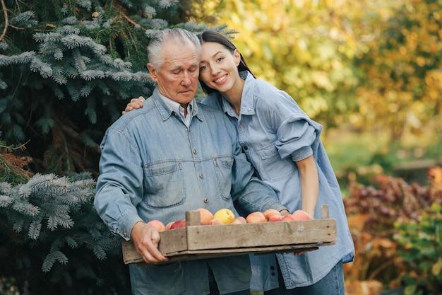 Ancien senior debout dans un jardin d'été avec récolte