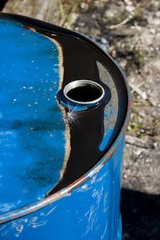 Ancien tambour à huile avec de l'huile noire sur le dessus qui a piégé une graine de pissenlit