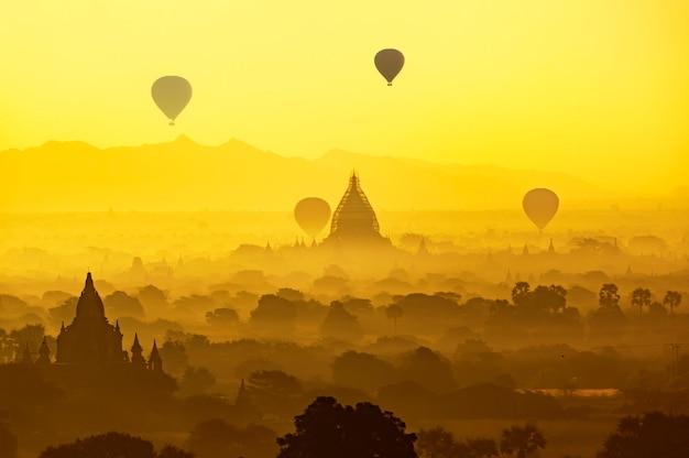 Ancien temple et montgolfière survolent le ciel à bagan après le lever du soleil