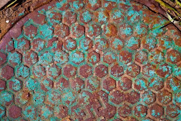 Ancien trou d'homme rouillé avec des traces de peinture écaillée bleue.
