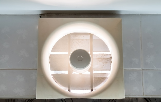 L'ancien ventilateur fonctionne sur le mur au-dessus de la porte de la cuisine pour absorber les odeurs de nourriture lors de la cuisson dans la cuisine, vue de face pour l'espace de copie.