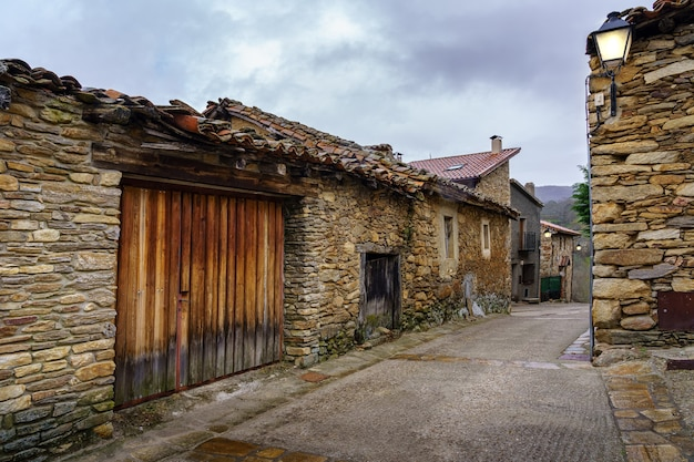 Ancienne allée de maisons en pierre avec des lampadaires avec lumière allumée au coucher du soleil par temps nuageux. madrid.