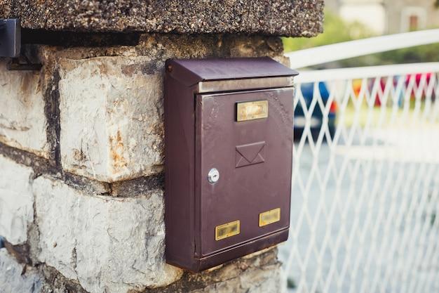 Ancienne boîte aux lettres rétro marron métallique sur le mur