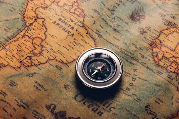 Ancienne boussole découverte sur papier vintage carte du monde antique, navigation de géographie de voyage de cartographie de style rétro
