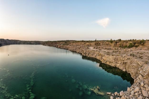 Ancienne carrière de pierre inondée avec de grosses pierres le soir, lumière chaude et lumineuse recouverte de petites plantes sèches dans la pittoresque ukraine. tir de drone panoramique aérien