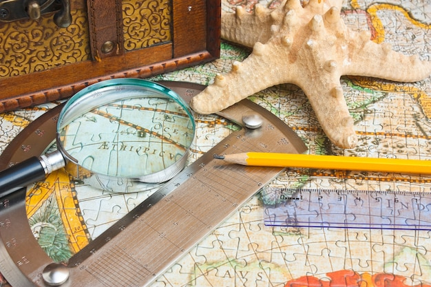 Ancienne carte et une boucle avec un rapporteur, nature morte