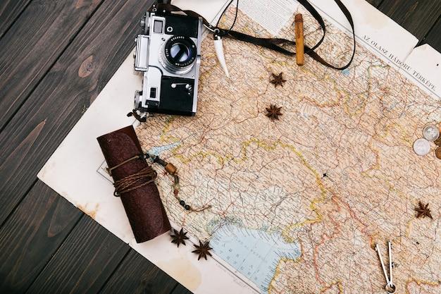 Ancienne carte jaune, lunettes, pièces de monnaie, étui en cuir, appareil photo, montre, boussoles, grains de café, d'autres épices et biscuits se trouvent sur le plancher en bois