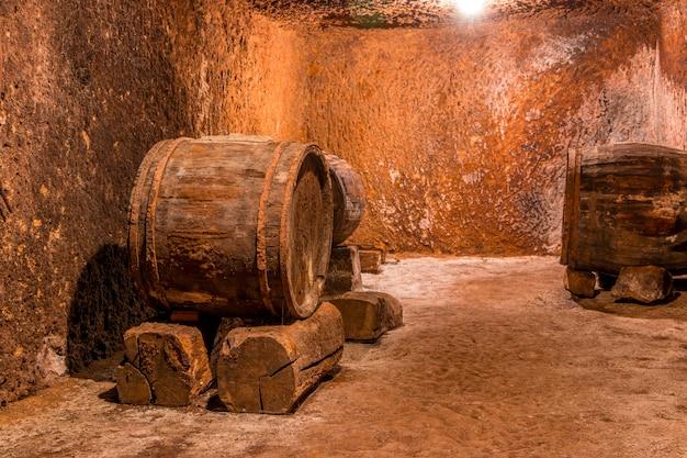 Ancienne cave à vin aux murs texturés. grands fûts de chêne sur les dessous de verre en pierre