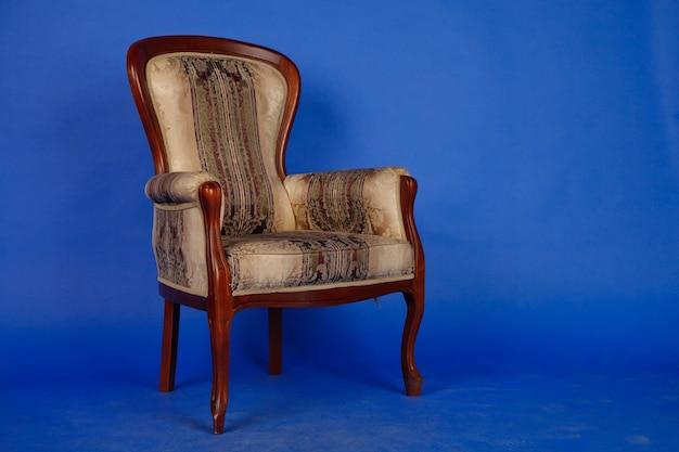 Ancienne chaise rétro en velours sur fond bleu royal sans intérieur. canapé capitonné marron antique pour un salon élégant. chaise design vintage sur fond sombre. style classique. espace de copie