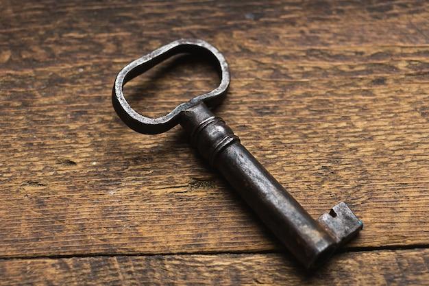 Ancienne clé sur un mur en bois sombre.