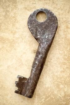 Ancienne clé rouillée sur fond de carton vintage