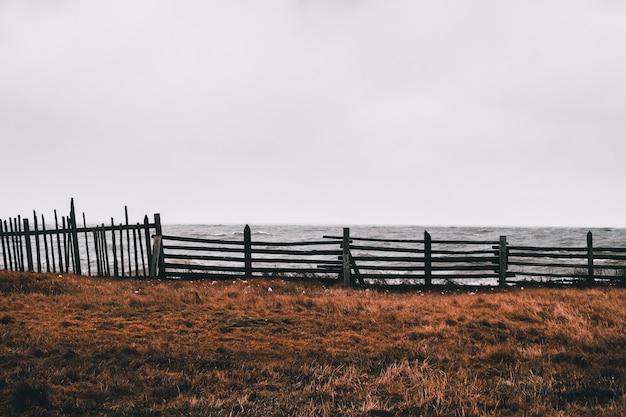 Ancienne clôture de pêche d'un ciel dramatique sur la plage. russie.