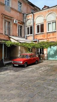 Ancienne cour soviétique typique avec voiture rouge
