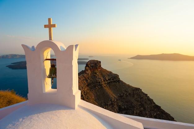 Ancienne église au coucher du soleil sur l'île de santorin, grèce. beau paysage marin d'été. destinations de voyage célèbres
