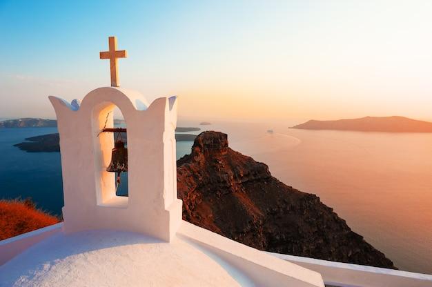 Ancienne église au coucher du soleil sur l'île de santorin, grèce. beau paysage marin d'été.