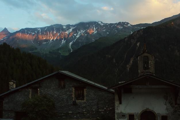 Ancienne église entourée de montagnes et d'arbres