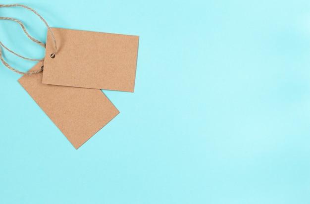 Ancienne étiquette de tissu de papier vierge ou étiquette sur fond bleu.
