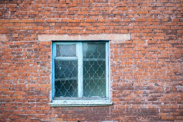 Ancienne façade murale minable d'un immeuble en brique avec des fenêtres en verre en bois de couleur turquoise. le concept de pauvreté, de corruption et de destruction. photo de haute qualité