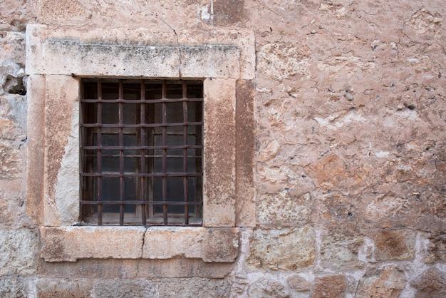 Ancienne fenêtre à barreaux, située dans une muraille médiévale