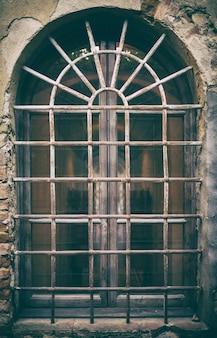 Ancienne fenêtre médiévale avec barres en fer forgé.