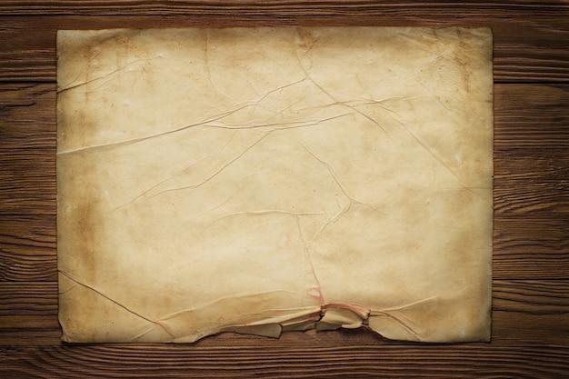 Ancienne feuille de papier horizontale cassée sur planche de bois brun