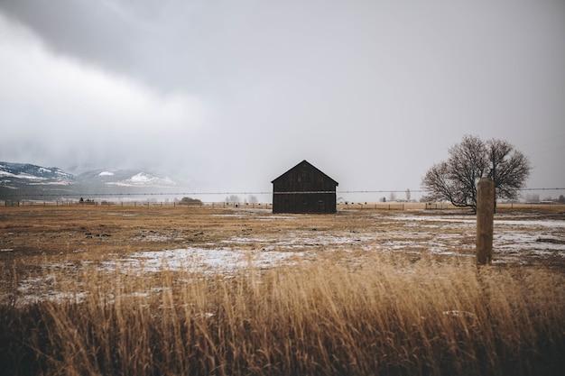 Ancienne grange en bois dans un champ entouré d'une clôture sous un ciel nuageux