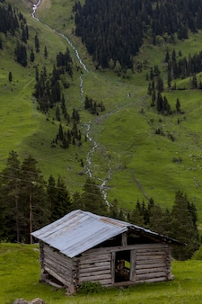Ancienne grange en bois entourée de forêts et de rochers avec la rivière