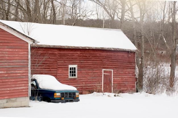 Ancienne grange rouge vintage abandonnée avec une vieille voiture restant à côté