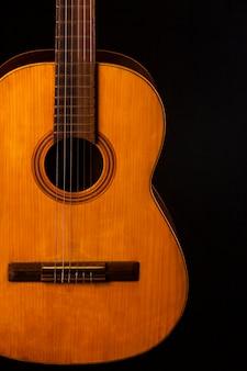 Ancienne guitare acoustique sur un mur noir.