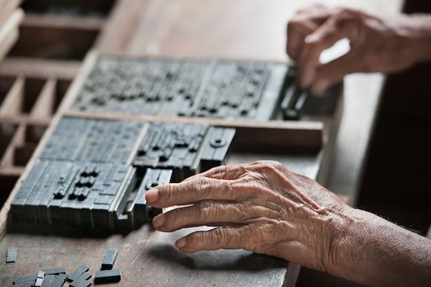 Ancienne industrie typographique. photo macro de l'homme qui met la lettre à la presse b