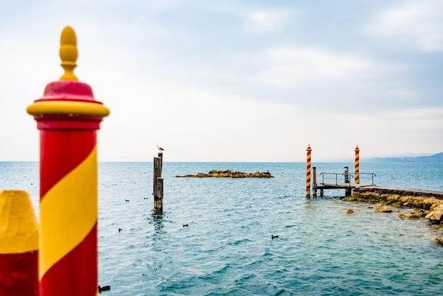 Ancienne jetée en pierre à la pointe de san vigilio, sur le lago di garda avec des poteaux d'amarrage colorés sur