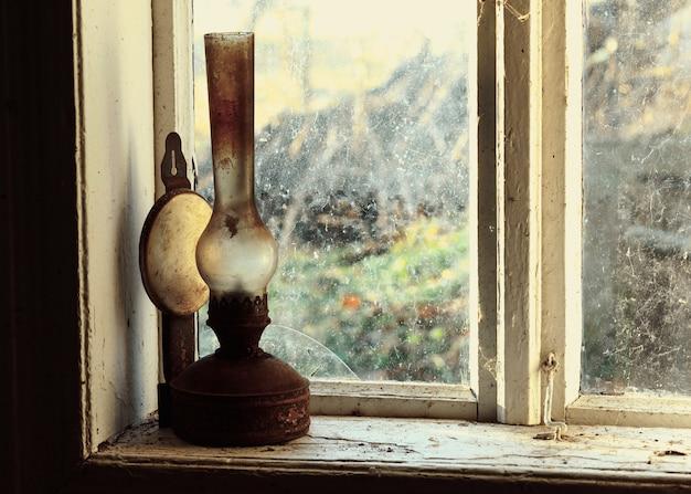 Ancienne lampe à pétrole sur une vieille fenêtre rustique rétro et vintage