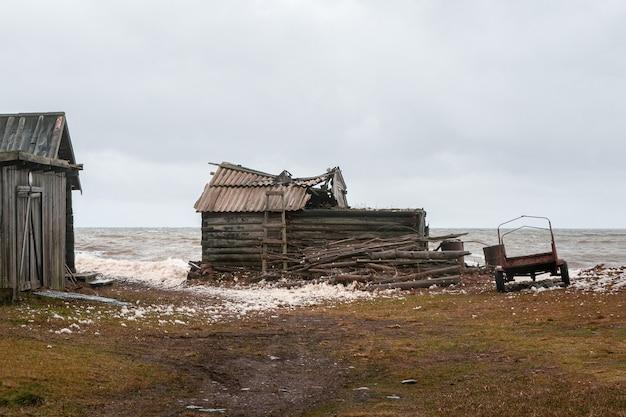 Une ancienne maison de pêcheur délabrée dans un village authentique au bord de la mer blanche