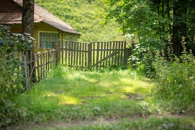 Ancienne Maison Rurale En Bois Dans Une Région Montagneuse Des Carpates. Bâtiment Traditionnel. Cour Avec De L'herbe Verte. Photo Premium